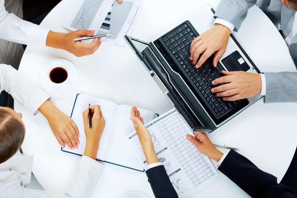 צוות יושב בשולחן עם לפטופ ונתונים