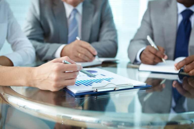 ייעוץ כלכלי, צוות יושב סביב שולחן עם דפי נתונים